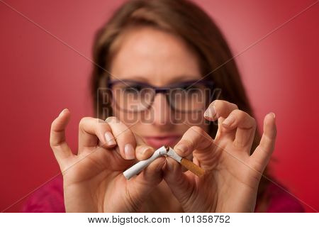 Beautiful Young Woman Breaks A Cigarette As A Gesture For Quit Smoking