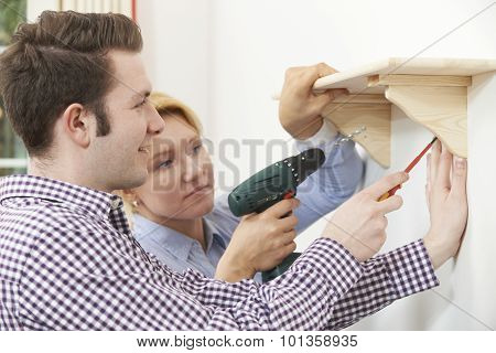 Couple Putting Up Wooden Shelf Together At Home