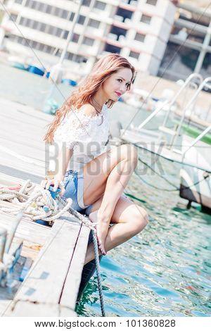 Beautifu Young Girl Sitting On The Wharf