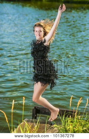 Lifestyle Concept: Portrait Of Happy Smiling Woman Making A High Jump Near Water Shore.