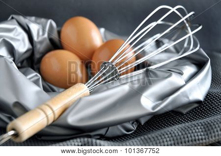 Close Up Whisk With Eggs On Background