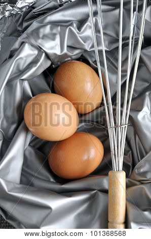 Eggs With Whisk On Silver Background