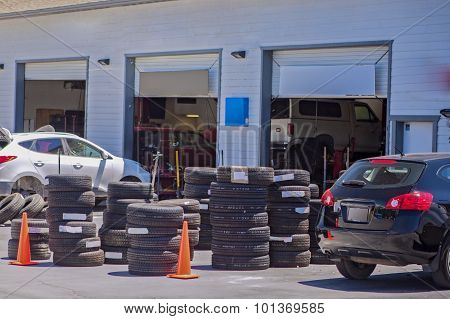 Standard American Auto Repair Shop During Its Working Hours. Stacks Of New Black Tyres Outside
