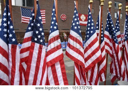 US flags in front of memorial wall