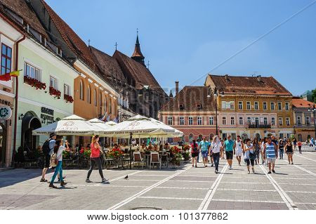 Brasov, Romania - 6th July 2015: Council Square is historical center of Brasov, Romania. People walkinng and sitting at outdoor terraces and restaurants. Black Church can be seen at background.