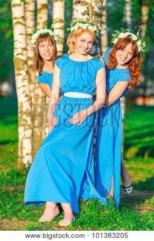Girls In Blue Dresses With Wreaths On Heads Posing Near The Birch