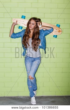 Beautiful Long-haired Woman With A Wooden Longbord Near A Green Brick Wall