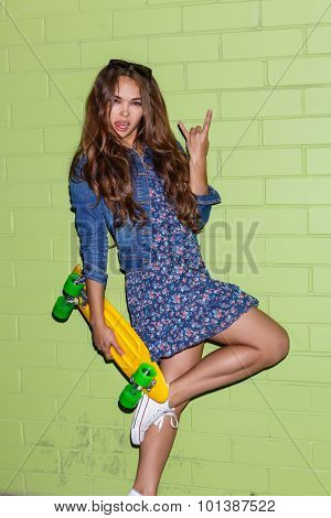 Beautiful Long-haired Lady With A Plastic Penny Board Near A Green Brick Wall