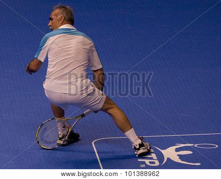 LONDON, ENGLAND. 05 DECEMBER 2009 -   Mansour Bahrami (FRA) plays a shot through his legs while competing in the ATP Champions Tour match between Leconte, Woodforde vs Bahrami, Fleming.