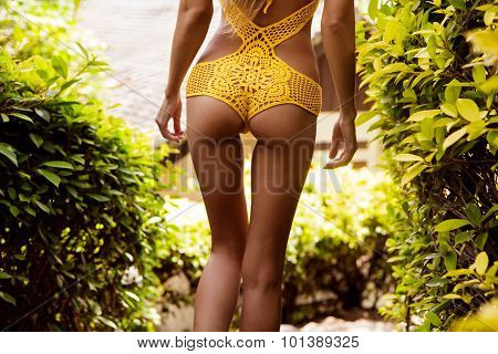 Pretty Athletic Girl In A Yellow Bikini Sexy Knit On The Footpath In A Tropical Garden