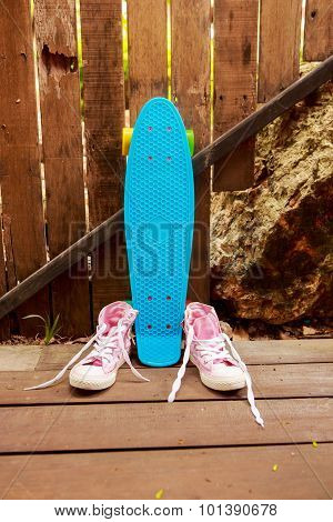 Pink Converse Sneakers Near Blue Skate Which Stands Near Wooden Fence