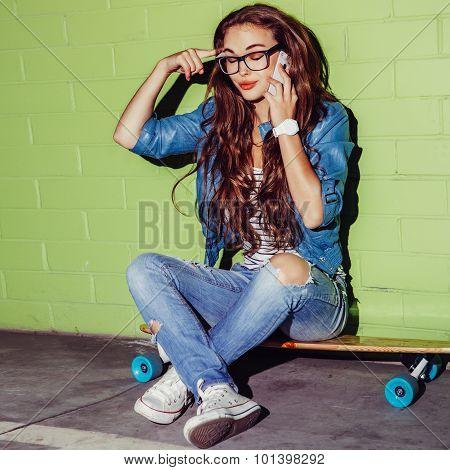 Beautiful Long-haired Woman With A Smatrphone Like Iphone Near A Green Brick Wall