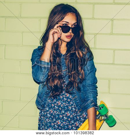Beautiful Long-haired Girl With A Plastic Penny Board Near A Green Brick Wall