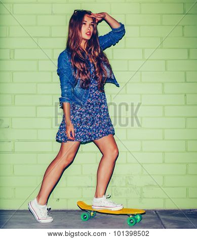 Beautiful Long-haired Woman With A Plastic Penny-board Near A Green Brick Wall