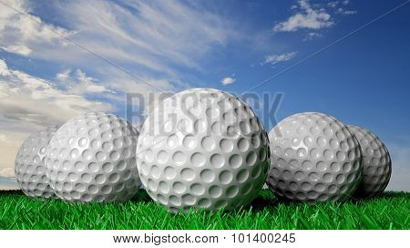Golf balls on green turf, with blue sky in background
