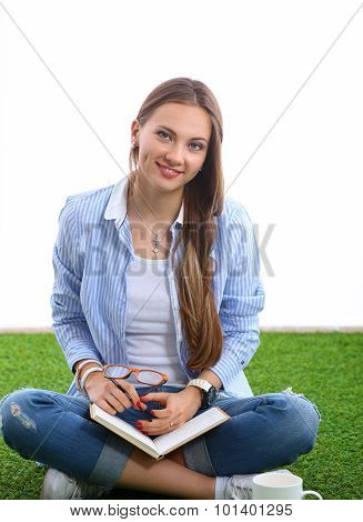 A young student studying in the park with textbook