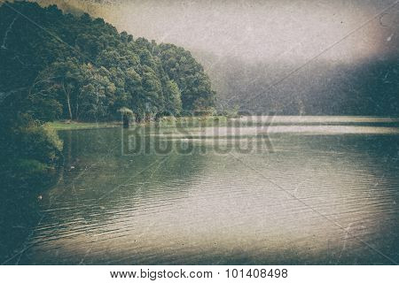 Vintage retro landscape - peaceful lake near foggy forest