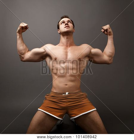 Athletic guy showing his muscles - winner victory concept