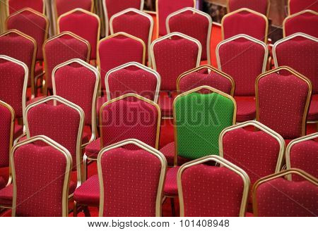 Diversity, different or unique concept - green chair in a group of red ones