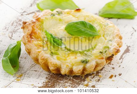 Tart With Cheese On A White Wooden Background.