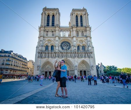 Couple takes a selfie of themselves in front of Notre-Dame Cathedral