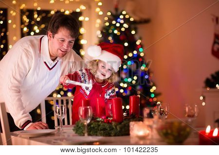 Father And Daughter Lighting Christmas Candles
