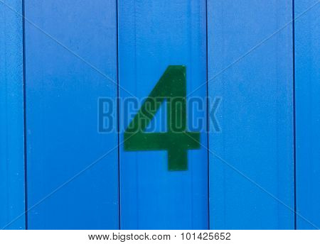 the number four, green, set against bright blue wood