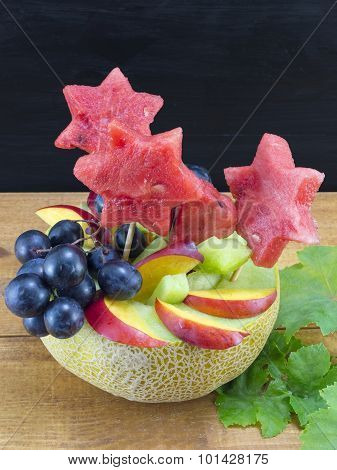 Healthy Attractive Fruit Salad Served In A Fresh Melon Against Black Wooden Background