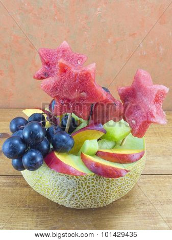 Healthy Unique Fruit Salad Served In A Fresh Melon On A Wooden Table