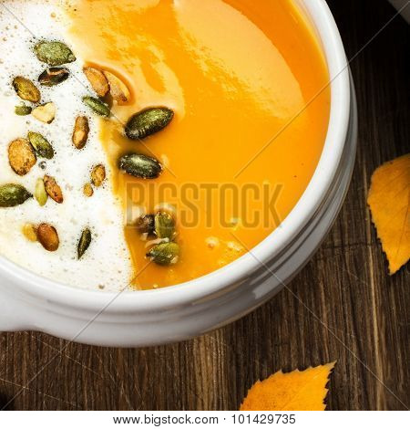 Pumpkin Soup With Whipped Cream And Pumpkin Seeds In A White Plate Over Wooden Background.  Beautifu
