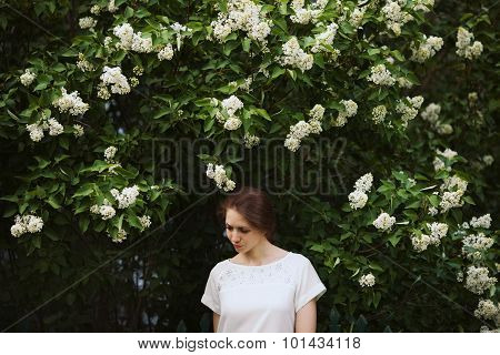 Woman Standing Next To A Bush Of White Lilac