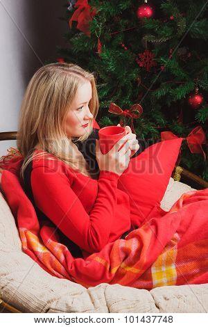 Sad woman sitting alone nearby Christmas tree