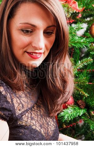 Lovely woman with long hair nearby Christmas tree
