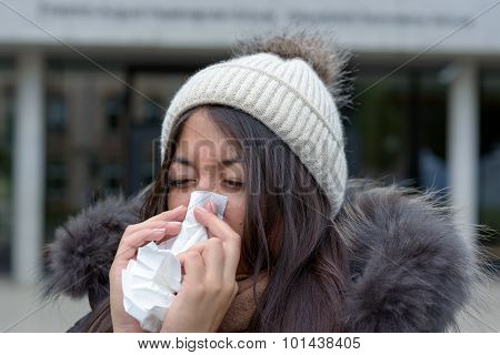 Young Woman With A Cold Blowing Her Nose