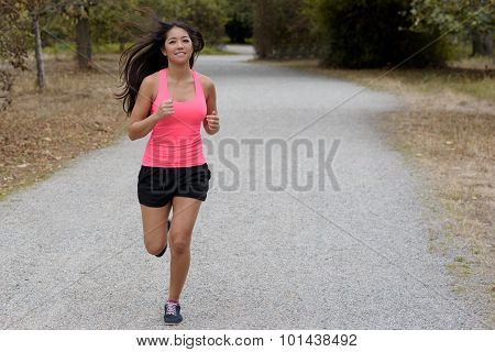 Fit Young Woman Jogging On A Country Road