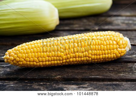 Close Up Fresh Ripe Sweetcorn On Old Wooden Table