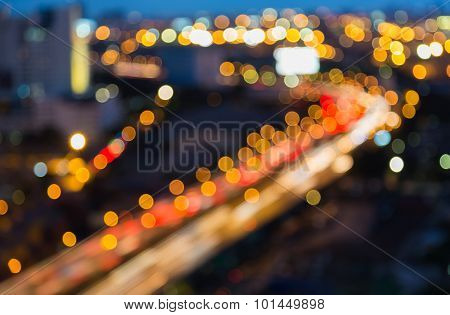 Abstract blurred bokeh light of City highway curved at night