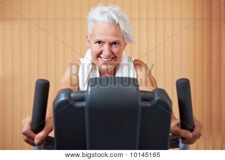 Elderly Woman On Bike In Gym