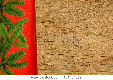 Red Cloth With Christmas Tree Branch Over Wooden Texture Close-up