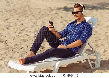Handsome freelancer lying on the beach