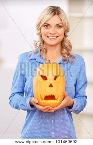 Pleasant woman holding pumpkin