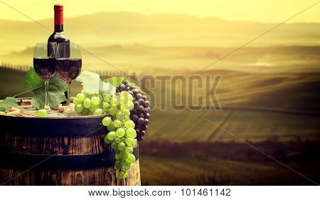 Red wine bottle and wine glass on wooden barrel. Beautiful Tuscany background