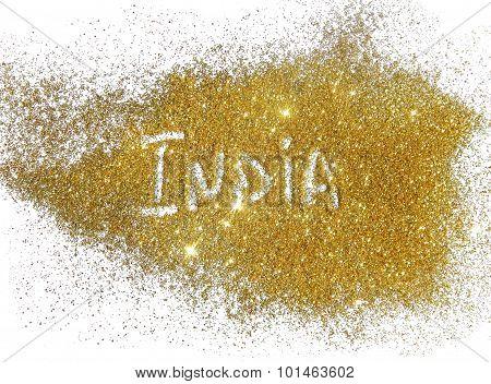 Inscription India on golden glitter sparkles on white background