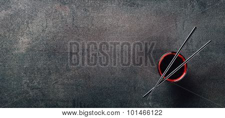 Chopsticks And Bowl With Soy Sauce On Textured Background