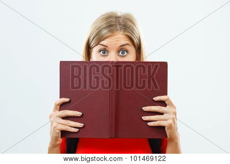 Student hiding behind book