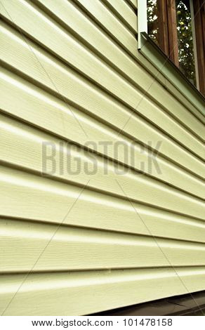 Wall Of The House With Light Color Siding At Close Range