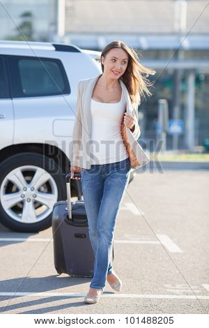 Attractive young woman with luggage is traveling