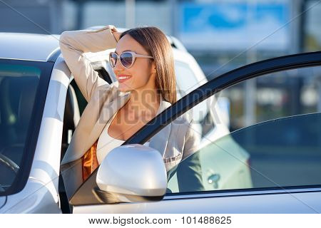 Attractive young businesswoman is resting near her transport