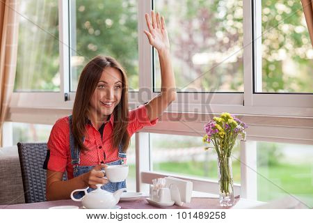 Cheerful young girl has meeting in cafe