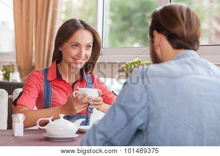 Cheerful young loving couple is resting in cafeteria